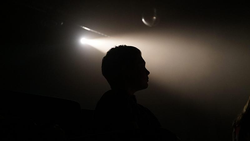 silhouette of man standing in darkness with one spotlight shining