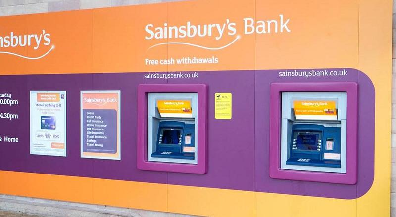 An outside wall with an orange mural and Sainsbury Bank ATMs
