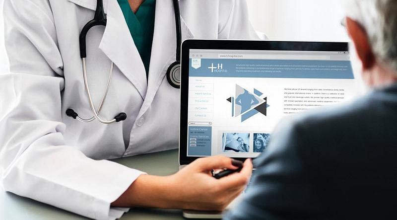 A doctor pointing at the information on a laptop screen in front of a patient